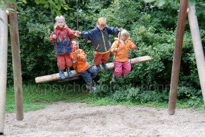 Vier Kinder auf einer langen Latte als Schaukel