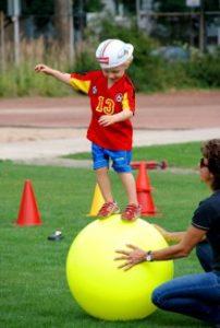 Junge balanciert auf Gymnastikball