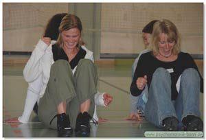 Frauen spielen sitzend Rückendrücken