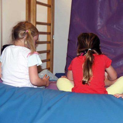 Kinder sitzen auf einer Matte in der Ecke