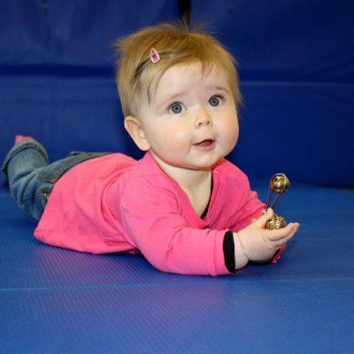 Baby in Bauchlage mit Greifling