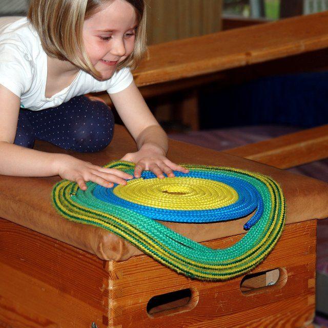 Mädchen legt einen Kreis aus Seilen