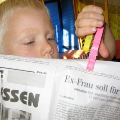 Psychomotorik-Alltagsmaterialien: Junge klemmt eine Wäscheklammer an eine Zeitung