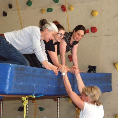Seminarteilnehmerinnen helfen einer Kollegin beim Klettern