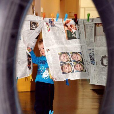 Kind geht durch einen Zeitungsvorhang
