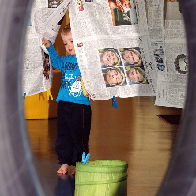 Kleinkind im Zeitungsvorhang