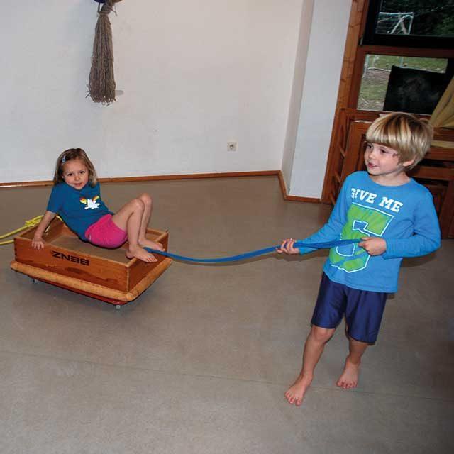 Junge zieht Mädchen vorsichtig im selbstgebauten Bollerwagen
