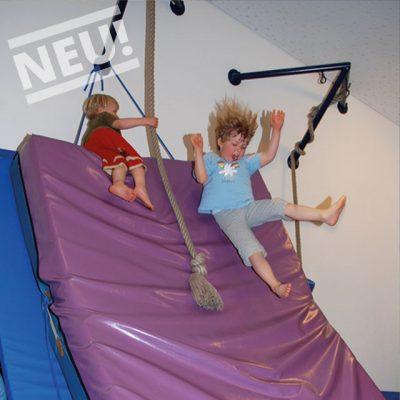Psychomotorik: Kinder rutschen eine Matte hinunter